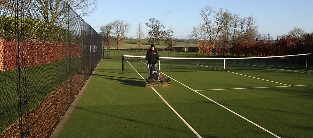 Elliott Courts - Brushing a tennis court to remove moss.