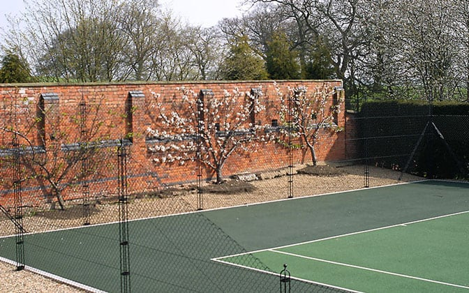 Pladek tennis court surface with obelisk fencing by Elliott Courts.